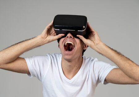 VR experience. Amazed and excited man using 360 VR headset goggles, feeling excited about simulation, making gestures having fun interacting with new virtual world. In Innovation and new technology. Archivio Fotografico