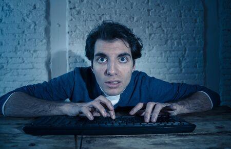 Süchtig junger Mann allein nachts auf Computer-Laptop-Arbeiten, Online-Glücksspiel, spätes Ansehen oder Spielen von Spielen zu Hause oder mit dem Internet-Chat-Social-Media-Netzwerk. Bei der Technologiesucht.