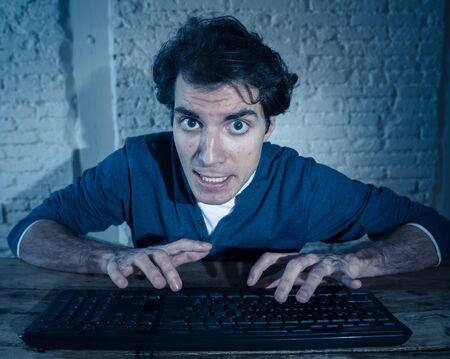 Addict jeune homme seul la nuit sur un ordinateur portable se sentant stressé et accablé d'essayer de terminer le travail ou de gagner un jeu ou un jeu en ligne. Dans la dépendance au travail et à la technologie Internet.