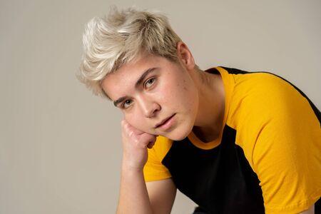 Portret młodej atrakcyjnej stylowej mody nastolatek pewny siebie i zadowolony ze swojej tożsamości płciowej. Trans chłopiec pozowanie w fajny miejski moda t shirt. W koncepcji piękna, osób transpłciowych i równości.