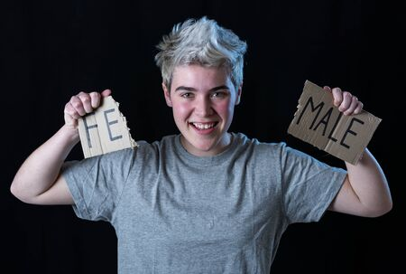 Handsome transgender teenager tearing the word Female into MALE in Gender identity, equality and human rights. Breaking silence about own gender identity transgender Pride and freedom concept.