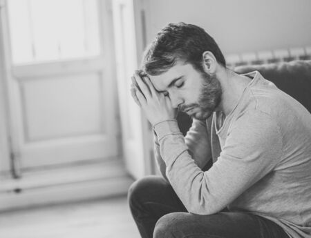 Unhappy depressed caucasian male sitting and lying in living room couch feeling desperate a lonely suffering from depression. In stressed from work, anxiety, heartbroken and men Health care concept.