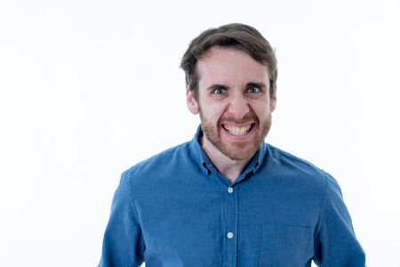 Close up portrait of young bearded man in his 20s making funny faces looking at the camera having fun. In humor and Positive Human facial expressions and emotions and young people. Imagens