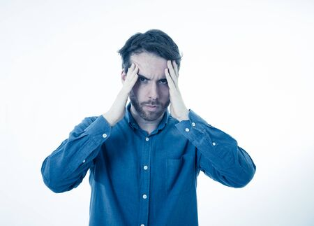 Portrait of a young bearded man looking worried and thoughtful suffering from migraines in great pain. Isolated on white background. In facial expressions and emotions and heath care concept. Imagens