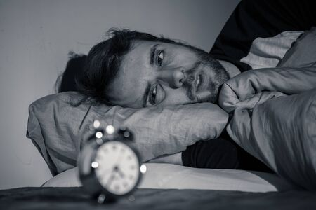 Sleepless and desperate young caucasian man awake at night not able to sleep, feeling frustrated and worried looking at clock suffering from insomnia in stress and sleeping disorder concept. Imagens