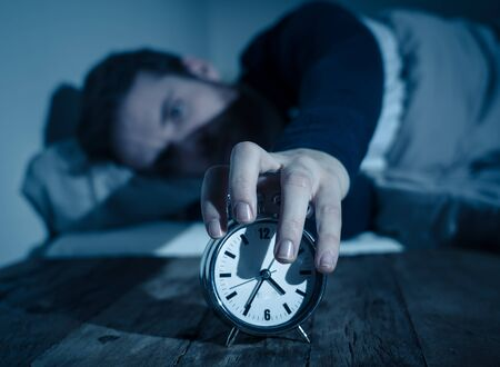 Insomnia Stress and Sleeping disorder concept. Sleepless desperate young caucasian man awake at night not able to sleep, feeling frustrated and worried looking stressed and concerned at alarm clock.