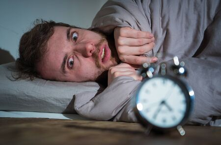 Mental health, Insomnia and sleeping disorders. Frustrated and hopeless sleepless man looking in distress at alarm clock awake at night not able to sleep suffering anxiety caused by stress at work. Imagens