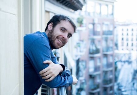 Happy good looking bearded man smiling enjoying urban view on outdoor balcony. Happy young hipster in European city relaxing on room balcony. Home comfort lifestyle and traveling around Europe.