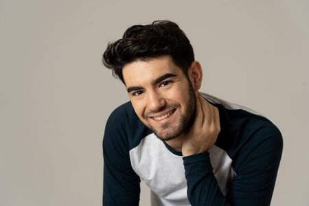 Positive human facial expressions and emotions. Portrait of handsome young male in his 20s with happy face smiling and making cheerful gestures at the camera. Close up Isolated on neutral background. Stock Photo