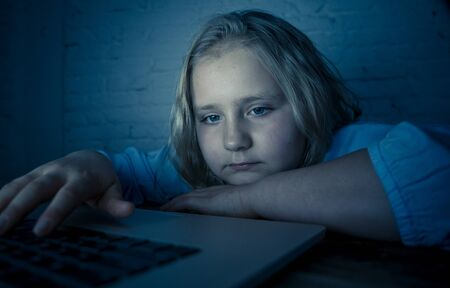 Scared sad girl bullied online on laptop suffering cyber bullying harassment. School girl humiliated on the internet by classmates feeling desperate and intimidated. Children victim of bullying.