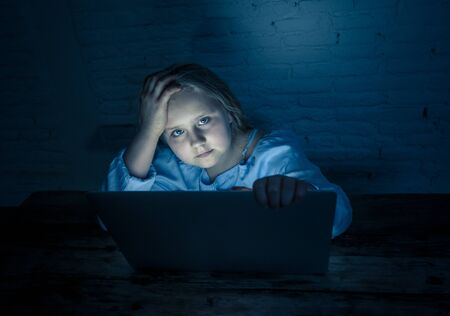 Scared sad girl bullied on line with laptop suffering cyber bullying harassment feeling desperate and intimidated. Child victim of bullying stalker social media network and the dangers of internet.
