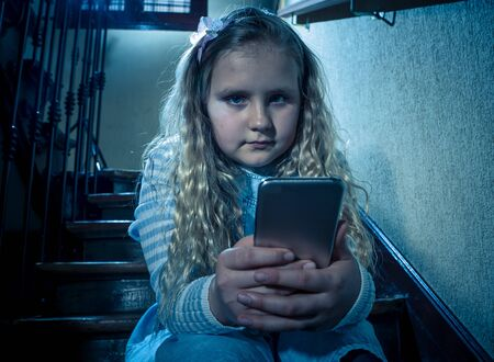 Sad depressed girl Bullied by text message humiliated online social media by classmates. Sad depressed young girl victim of cyberbullying by mobile phone sitting on stairs feeling lonely hopeless.
