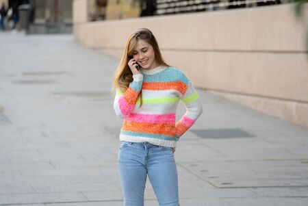 Pretty happy teenager woman talking on mobile smart phone outside city street. Beautiful stylish college student wearing fashion clothes feeling relaxed and free. Lifestyle, beauty and technology use.
