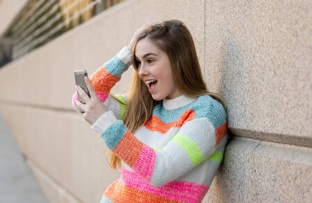 Pretty teenager woman happy and excited on smart mobile phone checking surprised lots of likes and followers on her blog. Urban background. In technology Communications online Trends and Blogging. Stock fotó