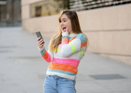 Pretty teenager woman happy and excited on smart mobile phone checking surprised lots of likes and followers on her blog. Urban background. In technology Communications online Trends and Blogging. Stock Photo