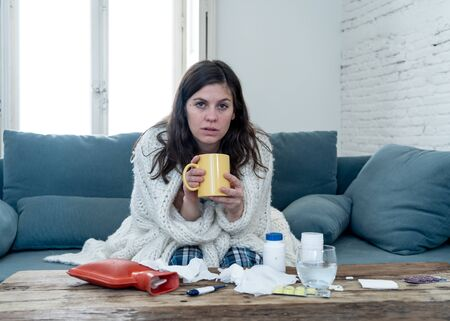 Sick young woman sitting on sofa drinking hot drink cold flu medicine feeling unwell with headache sore nose and high temperature not being able to go to work. Health care and medical concept. Zdjęcie Seryjne