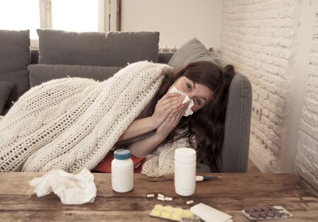 Sick woman on sofa sneezing and blowing her nose with allergy, hay fever or cold feeling unwell, fatigue and restless not being able to go to work. Lifestyle portrait In Health Care and medical. 写真素材