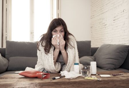Sick woman on sofa sneezing and blowing her nose with allergy, hay fever or cold feeling unwell, fatigue and restless not being able to go to work. Lifestyle portrait In Health Care and medical. 版權商用圖片