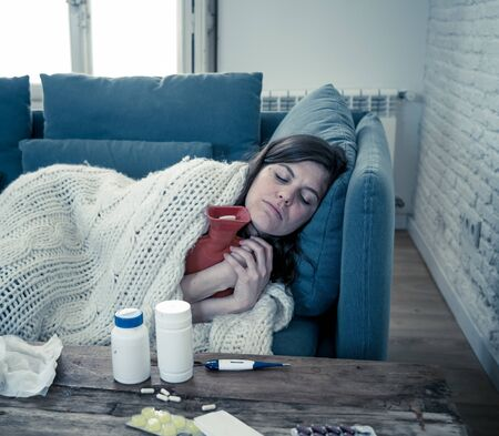 Sick attractive woman with hot water bottle lying on sofa at home feeling unwell with headache sore nose high temperature not being able to go to work. Col flu and Illness in Health Care concept. Zdjęcie Seryjne