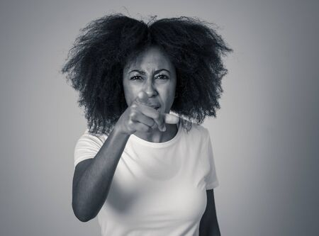 Portrait of attractive frustrated african american woman with angry and stressed face. Looking mad and crazy shouting and making furious gestures. Facial expressions and emotions and mental health.