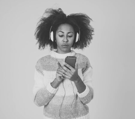 Colorful portrait of gorgeous and happy african american woman listening to smart phone music app in headphones singing and dancing on neutral background. In people Music Technology and Happiness. Banco de Imagens