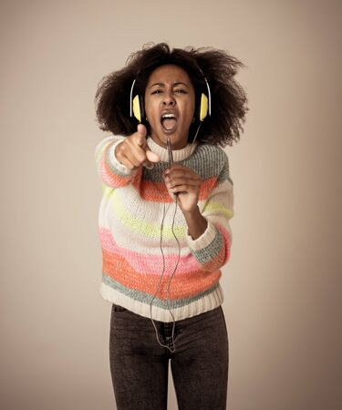 Colorful portrait of gorgeous and happy african american woman listening to smart phone music app in headphones singing and dancing on neutral background. In people Music Technology and Happiness. Zdjęcie Seryjne