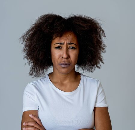 Portrait of african american woman in pain with sad and exhausted face looking concerned, worried and thoughtful in human emotions Mental health and Depression. Isolated on neutral background.