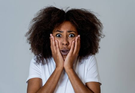 Portrait of young african american woman feeling scared and shocked making fear, anxiety gestures. Looking terrified covering herself. Copy space. In negative human expressions and emotions concept.