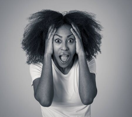 Beautiful shocked african american woman looking and pointing at something unbelievable or having great success with surprised and happy face and gestures. In People and human emotions and expressions.