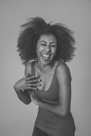 Happy portrait of beautiful young african american female laughing and enjoying life posing in red summer top. Image friendly for advertising. People fashion Human emotions and expressions.