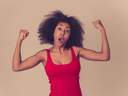 Portrait of young beautiful funny african american woman with afro hair style showing arms muscles smiling proud having fun. In people Success and Happiness. Human emotions and facial expressions.