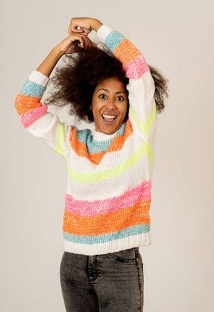 Portrait of happy young african american female laughing and having fun in multicolor striped jumper isolated over neutral background. People, human positive emotions and celebration life