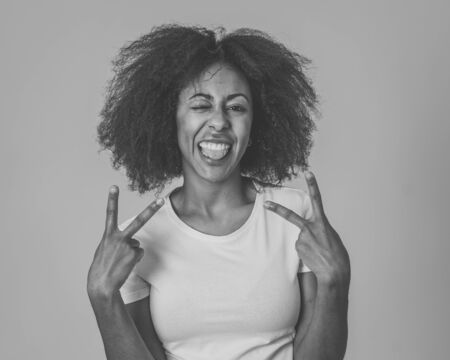 Portrait of attractive, confident african american young woman with happy facial expressions having fun posing. In People successful women and human emotions. Isolated on grey background.