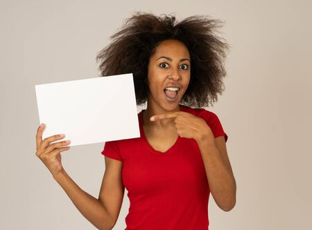 Funny and attractive young african american female showing and pointing at blank board with copy space for text. Cheerful mixed race woman holding blank poster for advertisement. Marketing concept.