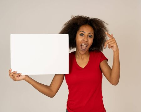 Attractive african american female showing blank poster with copy space for text looking excited as it shows a great product or amazing sale or great advertisement. studio shot. Marketing concept. Stok Fotoğraf