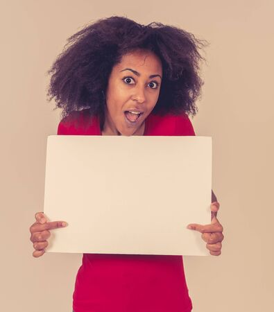 Beautiful african american young woman sowing and pointing at blank board with copy space for advertisement text. Looking happy surprised and shocked at great ad or product. In marketing concept. Banco de Imagens