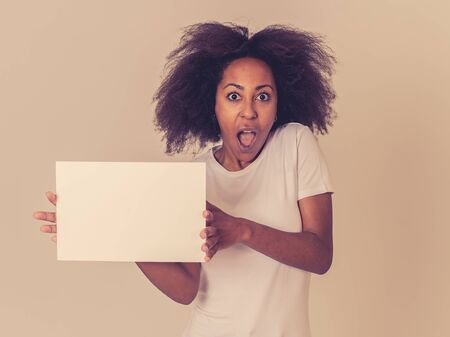Funny and beautiful african american woman showing and pointing at blank board with copy space for text. Friendly and excited woman with afro hair style holding blank poster. In Marketing concept.