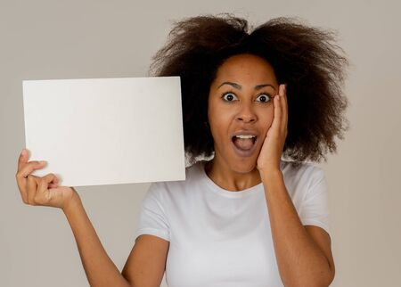 Funny and attractive african american woman showing blank poster with copy space for text looking excited as it shows a great product or amazing sale or great advertisement. Marketing concept.