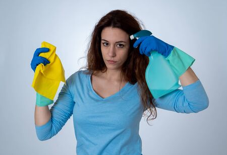 Beautiful angry and upset woman holding mop and cleaning spray feeling frustrated and furious in domestic duties concept and gender stereotypes. Studio portrait isolated on blue background.