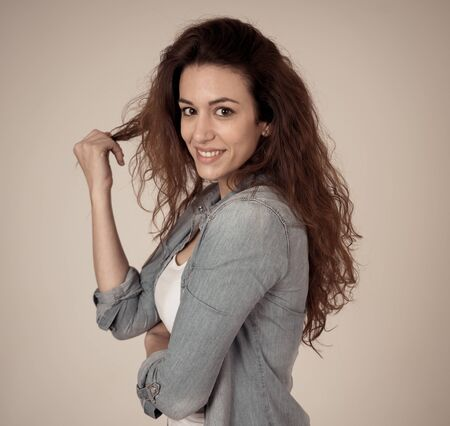 Close up portrait of young beautiful woman with happy face, beautiful smile and long curly red hair. Posing in jeans shirt and staring at the camera smiling. In Beauty Care Fashion Modeling concept. Фото со стока