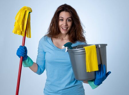 Beautiful happy housewife woman holding cleaning equipment. Proud women, Cleaning service Professional, housemaid and housework. Studio portrait isolated on blue background with copy space.
