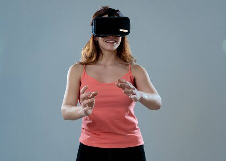 Amazed attractive woman using VR headset glasses touching and interacting with virtual reality world. Feeling excited exploring and having fun in 360 VR simulation. Innovation and new technology.