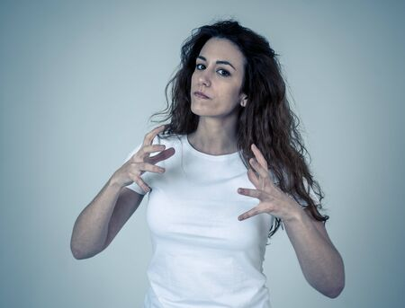 Close up portrait of attractive frustrated caucasian woman with angry and stressed face. Looking mad and crazy shouting and making furious gestures. Copy space. Facial expressions and emotions.