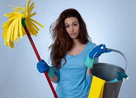 Young beautiful upset housewife woman holding bucket mop cleaning spray feeling stressed tired and frustrated in domestic duties and gender roles concept. Studio shot isolated on blue background.