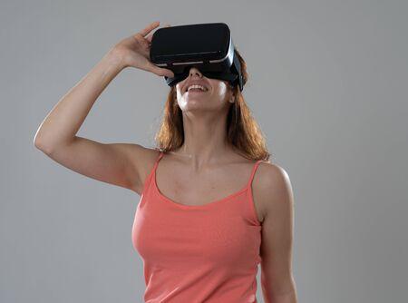 Neugierige Frau, die glücklich und aufgeregt ist, eine Virtual-Reality-Brille zu verwenden, die sich für die Simulation begeistert und das virtuelle Leben mit glücklichen Gesten erforscht Im Konzept der neuen Technologie Virtual Augmented Reality.