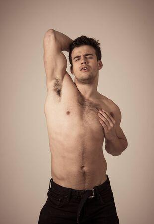 Portrait de bel homme athlétique avec torse fort posant viril pour la caméra. Prise de vue en studio d'un modèle publicitaire de fitness latin pour le sport, la beauté ou la mode isolé sur fond neutre.