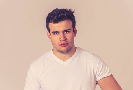 Close up portrait of an attractive young man with angry face looking furious and mad Isolated on neutral background. Studio shot In People, negative emotions and facial expression.
