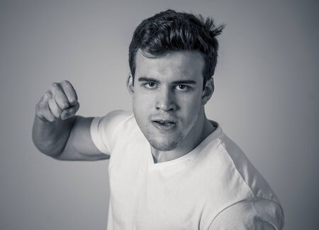 Young attractive man in rage looking furious in defence stance and threaten punching with fist in angry upset and mad face expression isolated grey background in youth violence and aggression concept.