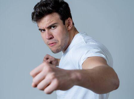 Hombre atractivo joven con rabia que parece furioso en posición de defensa y amenaza con puñetazos con el puño en expresión de enojo molesto y enojado aislado fondo gris en concepto de violencia y agresión juvenil.