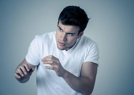 Retrato de joven latino guapo en estado de shock con una expresión de miedo en su rostro haciendo gestos de miedo y defensa en las emociones humanas, sentimientos y expresiones faciales. Tiro del estudio. Foto de archivo